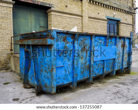 A dumpster/waste skip standing in front of a brick building. Refuse can be seen over the top edge of the skip. The skip itself is blue with lots of rust and dents. - stock photo