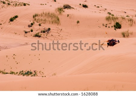 A dune buggy curls around the side of a large sand dune in a state park in Utah. - stock photo