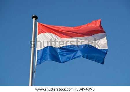 A Dutch flag with a blue sky in the background. - stock photo