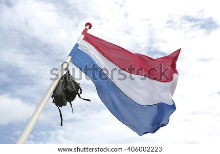 A dutch flag with a school bag in top to celebrate graduation - stock photo