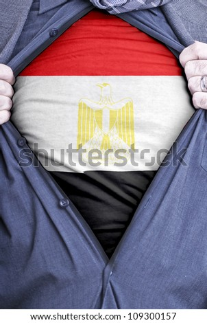 A Egyptian businessman rips open his shirt and shows how patriotic he is by revealing his countries flag beneath printed on a t-shirt - stock photo