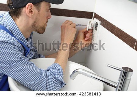 A Electrician changing a socket outlet in bathroom - stock photo