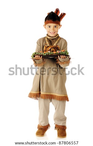 """A elementary """"American Indian"""" boy presenting a plateful of roasted poultry and vegetables.  On a white background. - stock photo"""