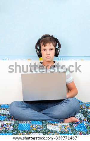 A eleven years boy is working on laptop at home  - stock photo