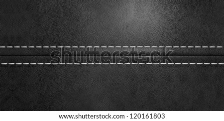 A fabricated stitched seam joining two pieces of black leather together - stock photo