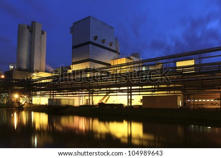 A factory near a river by night. - stock photo