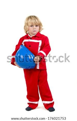 A fair haired little boy has a fireman suit on. - stock photo