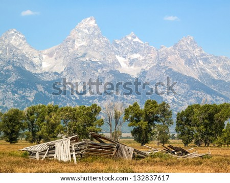 A fallen barn on Mormon Row with the Cathedral Group of the Teton Range in the Antelope Flats area of Grand Teton National Park, Wyoming - stock photo