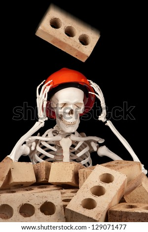 A falling brick is about to make contact with a hard hat on the skull of a skeleton. - stock photo