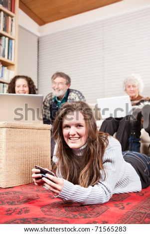 A family at home using wireless technology such as laptop and cell phone - stock photo