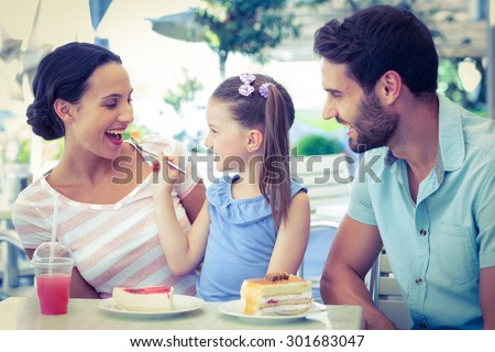 A family eating at the restaurant on a sunny day - stock photo