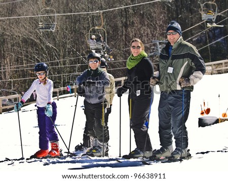 A family enjoying a holiday at the ski slopes. - stock photo