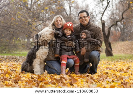 A family enjoying time together in a park during the Autumn season. - stock photo