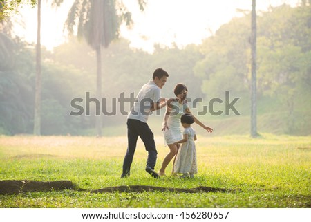 a family having fun playing in the early foggy morning - stock photo