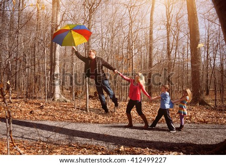 A family is holding hands together and flying up in a rainbow umbrella with sunlight outside for a imagination, support or happiness concept. Soft focus. - stock photo