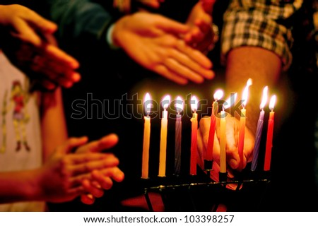 A family is lighting a candle for the Jewish holiday of Hanukkah that is observed for eight nights and days. - stock photo