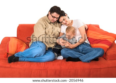 A family of a toddler son, a mother and a father are sitting on the couch together at home. They are reading a tales book. The image is isolated on white. - stock photo