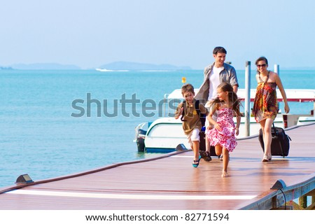 A family of 4 arriving at the resort with their luggage. - stock photo