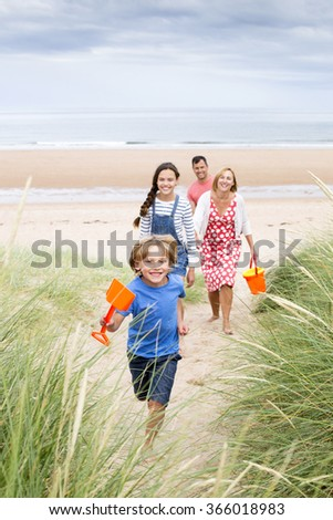 A family of four are walking up the sand dunes leaving the beach. The little boy is running up first smiling at the camera. - stock photo