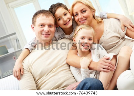 A family of four embracing and smiling at home - stock photo