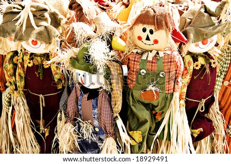 A family of scarecrows dressed in burlap and raffia. - stock photo