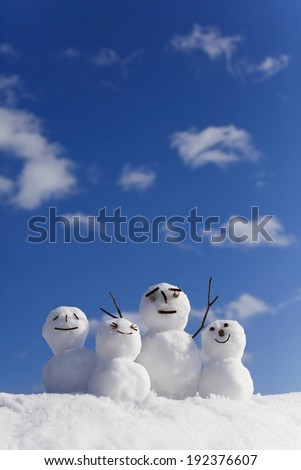 A family of snow people with a blue sky. - stock photo