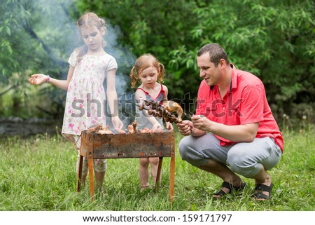 A family of three making barbecue on the grill on nature, focus on a father. - stock photo