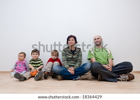 A family sitting in an unfurnished room of their new house. - stock photo
