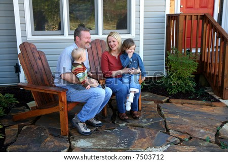 A family sitting in front of their home - stock photo