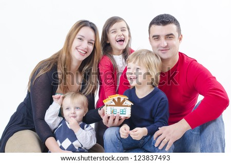 A family with three children holding a little house - stock photo