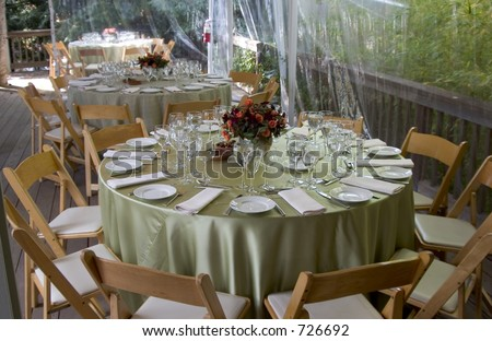 A fancy table setting awaits the guests.  Focus is on the forground plate and glasses. - stock photo