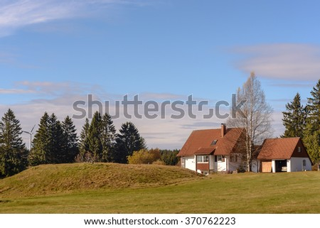 A farm is located on the green grassy hill. In the background there are mountains covered with a coniferous forest. - stock photo