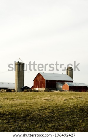 A farm with three buildings and two grain silos. - stock photo