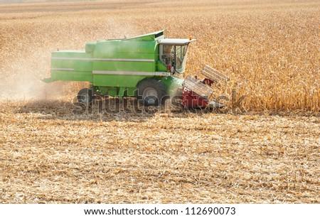 A farmer combines a field of corn - stock photo