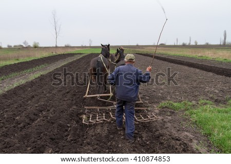 A farmer cultivates the land with the help of horses and harrows, hand, old-fashioned method. - stock photo