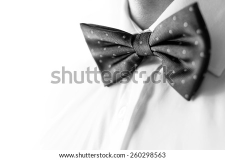 A fashionable groom wears a bowtie. A close-up shot of a man wearing a bowtie. B&W photo - stock photo