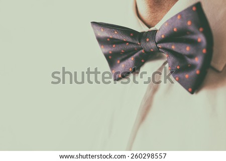 A fashionable groom wears a bowtie. A close-up shot of a man wearing a bowtie. Fashion colors - stock photo