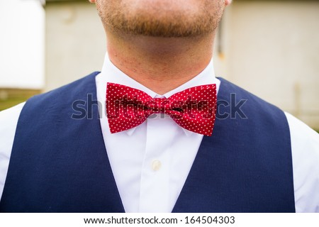 A fashionable groom wears a red and white bowtie with a navy blue vest on his wedding day. - stock photo