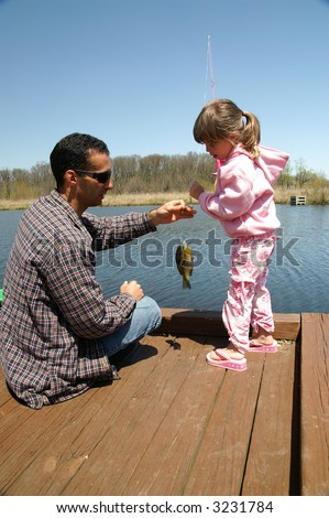 A father and daughter go fishing - stock photo