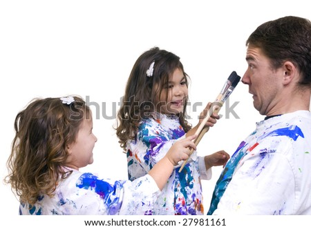 A father and his two daughters having fun painting. - stock photo