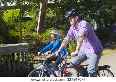 A father and his young daughter enjoy biking together in a beautiful summer afternoon. - stock photo