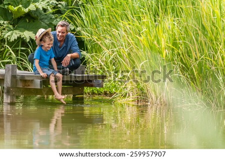 a father and his young son have good time together, they are sitting on a wooden pontoon in summertime - stock photo