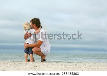 A father and his young toddler son are hugging as they stand on a white sand beach and look out over the ocean while on vacation. - stock photo