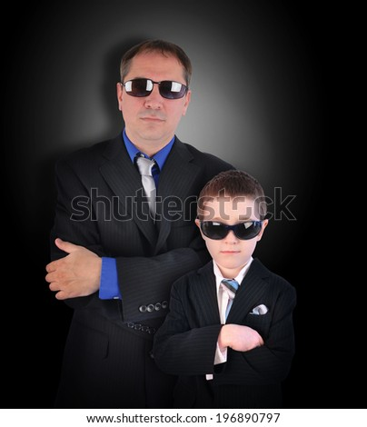 A father and son are wearing business suits with sunglasses pretending to be secret agents or bodyguards on a black background. - stock photo