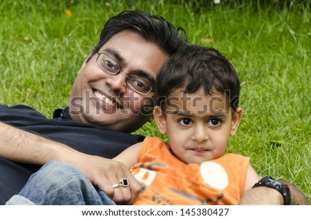 A father and son playing together in a garden. - stock photo