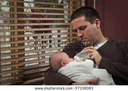 A father feeds his baby boy a bottle - stock photo