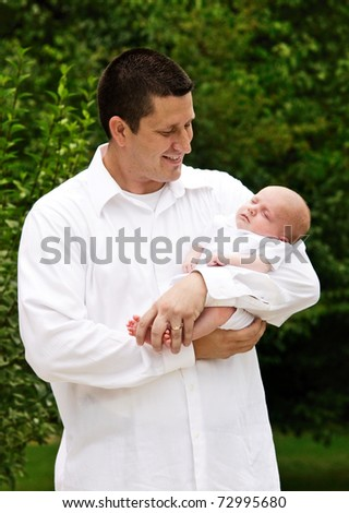 A father holding his newborn baby boy, vertical with shallow depth of field, natural light - stock photo
