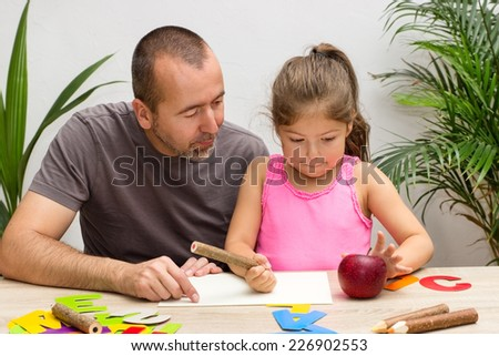 A father is exercising the alphabet with his little daughter - stock photo