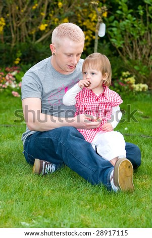 A father is helping his daughter with candy - stock photo