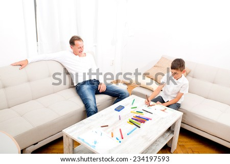 A father is sitting on the couch while his son is drawing.  - stock photo